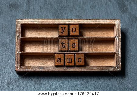 Yo te amo. I love you in Spanish translation. Vintage box, wooden cubes phrase with old style letters. Gray stone textured background. Close-up, up view, soft focus