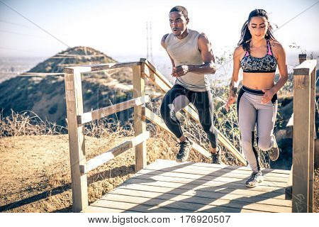 Couple running in los angeles canyons. making exercises after run