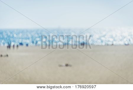Blurred beach concept with bathers lying on the sand