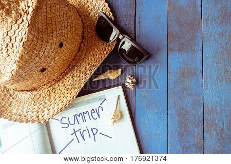 Hat with glasses calendar and seashells on blue painted wood plank background. Summer holiday concept
