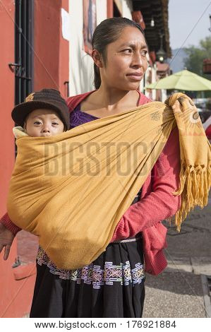 SAN CRISTOBAL DE LAS CASAS CHIAPAS MEXICO - FEBRUARY 20 2017: A Tsotsil woman carries her six-month-old baby in a traditional cotton shawl on a Monday morning as she begins her daily activities.
