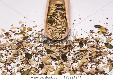 Sesame seeds, pumpkin seeds, sunflower seeds, chia seeds, flax seeds, poppy seeds and a wooden spoon