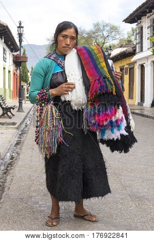 SAN CRISTOBAL DE LAS CASAS CHIAPAS MEXICO - FEBRUARY 20 2017: A Tsotsil woman wearing traditional wool skirt carries an assortment of colorful shawls bracelets and necklaces to sell to tourists visiting this culturally-rich city.