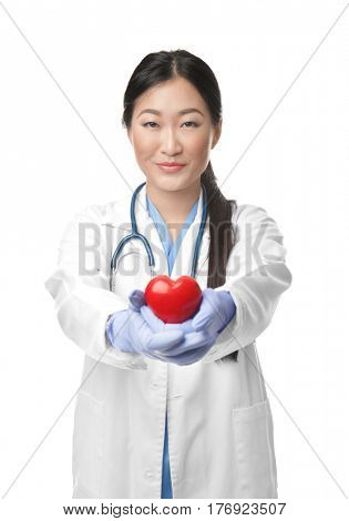 Pretty doctor holding red plastic heart on white background