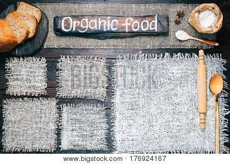 Rustic style template for food and drink industry. Burlap frames on dark wood background with flour pack and sliced bread. Wooden  signboard with text 'Organic food' as title bar