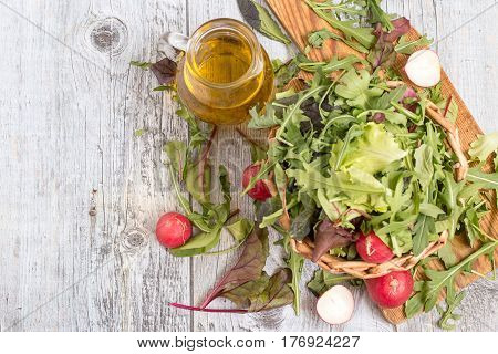 Ingredients for the preparation of spring salad. Fresh herbs such as chard, lettuce, beet leaves and a radish in a wicker basket on a cutting board, next to a glass jug with olive oil.