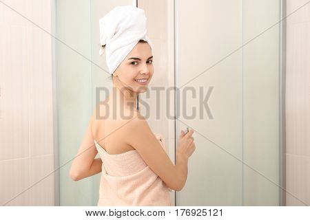 Beautiful young woman in towel going to shower
