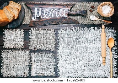 Rustic style template for food and drink industry. Burlap frames on dark wood background with flour pack and sliced bread. Wooden  cutting board with text 'Menu' as title bar