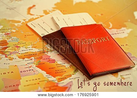 Passports with tickets and text LET'S GO SOMEWHERE on map background