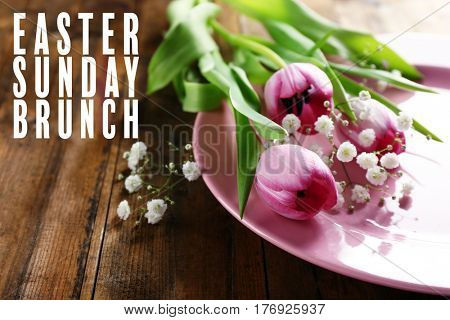 Text EASTER SUNDAY BRUNCH on background. Plate and flowers on wooden table