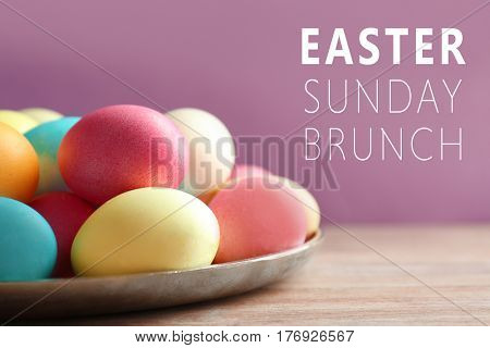 Text EASTER SUNDAY BRUNCH and colorful eggs on bright background