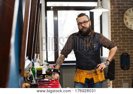 Experienced bearded barber at workplace in barbershop. Professional stylish hairdresser waiting for client at hair salon