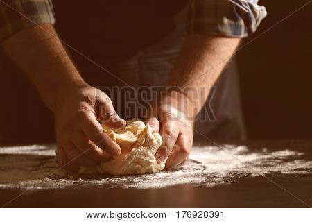 Man kneading dough in kitchen, closeup