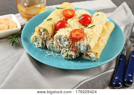 Delicious stuffed cannelloni with cherry tomatoes on blue plate