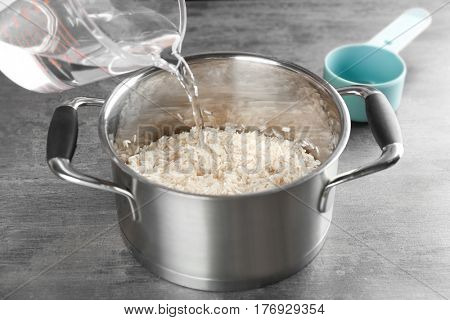 Cooking concept. Pouring water in saucepan with rice