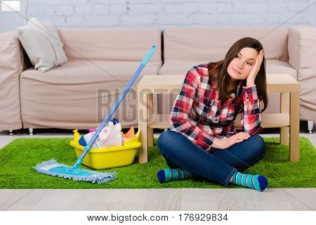 exhausted woman dressed in casual clothes sitting on the floor, during housework. Beside her cleaning supplies, mop for cleaning the house.