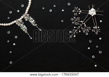 Handmade white gentle wedding bijouterie : earrings with crystals and white pearl necklace hairpins with crystals branches decoration lying flat on the vertical black background top view