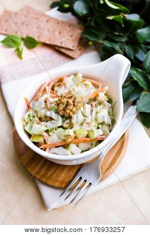 Fresh coleslaw salad with white cabbage, carrot, apples and pears with walnuts and yogurt dressing in a bowl, selective focus