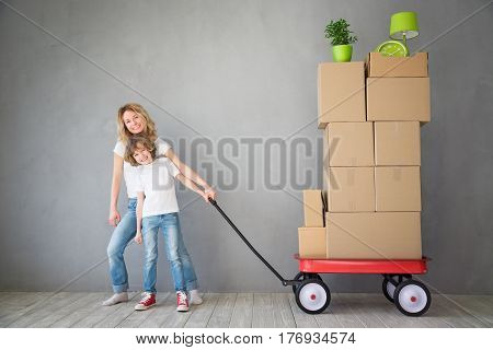 Happy family playing into new home. Father mother and child having fun together. Moving house day and express delivery concept