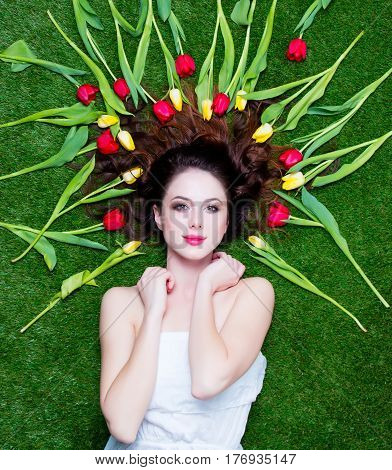 Beautiful Young Woman Near Yellow And Red Tulips  Lying On The Wonderful Green Grass Background