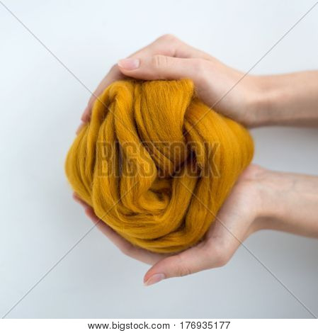 Close-up of brown merino wool ball in hands.