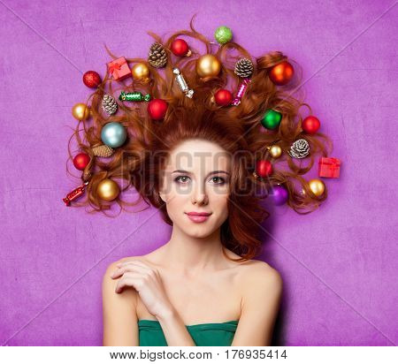 beautiful young woman with gifts candies baubles and cones in her hair lying on the wonderful purple background