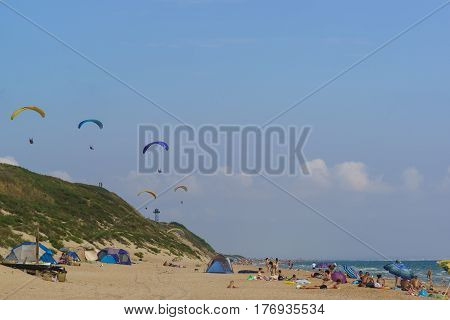 Anapa district Krasnodar Krai Russia - August 15.2015: Paragliders soaring over the wild sandy beach with tents and campers. Shore of the Black sea