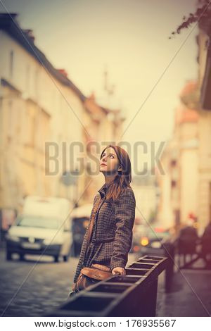 beautiful young woman standing on the street near fence and examine wonderful Wroclaw