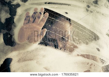 Stressed Man Taking A Shower Standing Under Flowing Water And Spends His Hand Over The Soap Foam In