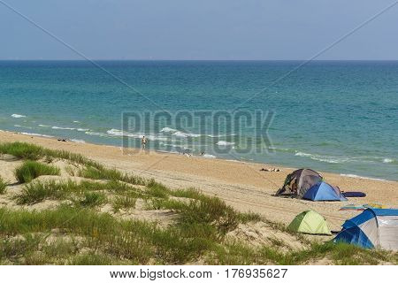 Anapa district Krasnodar Krai Russia - August 15.2015: a Man goes on a wild sandy beach with tents and campers. Shore of the Black sea