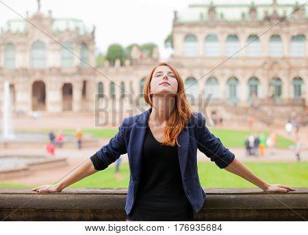 Beautiful Young Woman Relaxing On The Old Historic Building Background