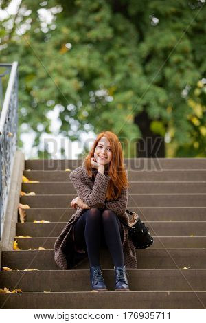 Beautiful Young Woman Sitting On The Stairs And Smiling
