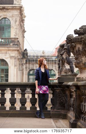 Beautiful Young Woman Standing On The Balcony Of Old Building