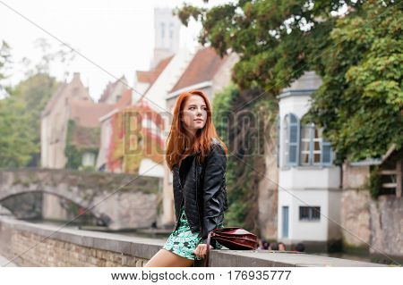 Beautiful Young Woman Sitting On The Stone Fence And Exploring The Town