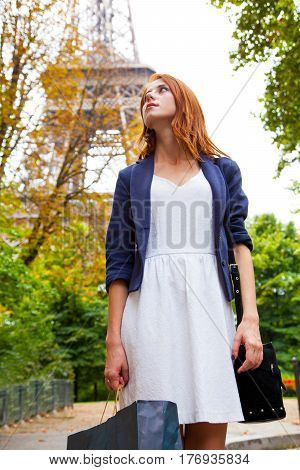 Beautiful Young Woman With Shopping Bag On The Eiffel Tower Background