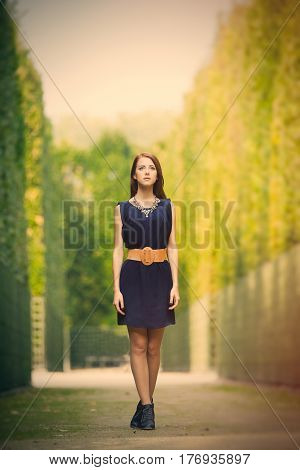 Beautiful Young Woman Standing In The Park Full Of Bushes