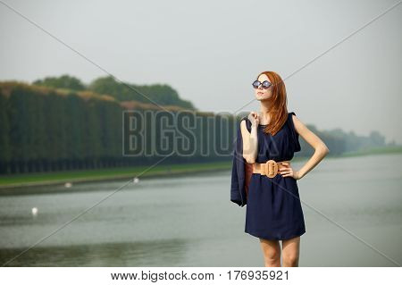 beautiful young woman standing in front of river and trees background