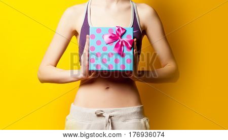 Photo Of Perfect Slim Female Body With Cute Gift In The Hands On The Wonderful Yellow Background