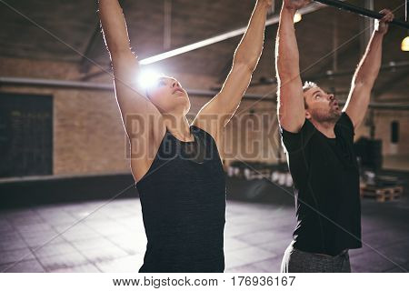 Two Sportsmen Doing Pull-ups While Working Out