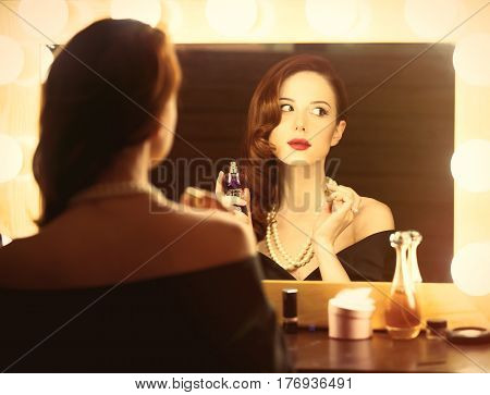 Photo Of Beautiful Young Woman Using Her Perfume Near The Window With Lights