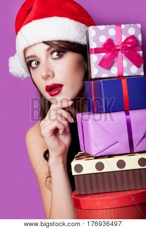 Photo Of Beautiful Young Woman With Gifts In Santa Claus Hat On The Wonderful Purple Background