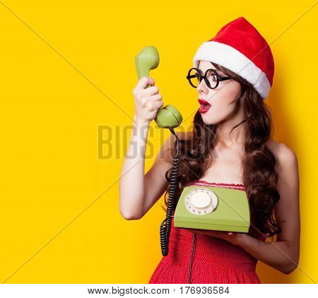 Photo Of Beautiful Young Woman With Retro Phone In Santa Claus Hat On The Wonderful Yellow Backgroun
