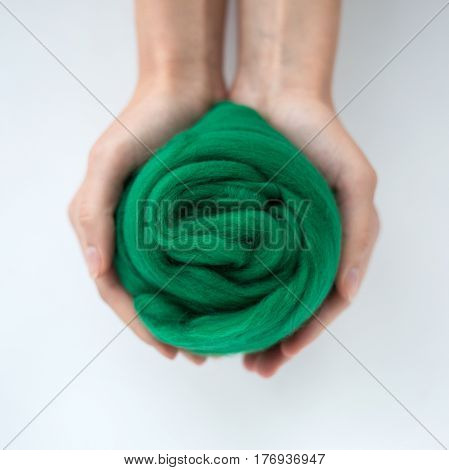Close-up of green merino wool ball in hands.