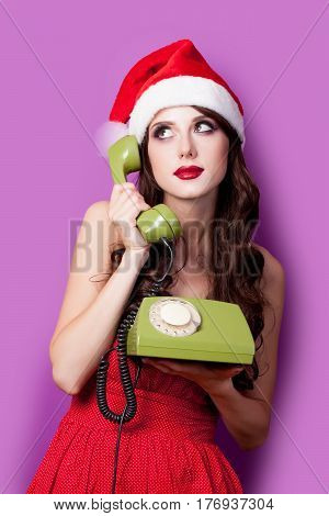 photo of beautiful young woman with retro phone in santa claus hat on the wonderful purple background