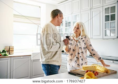 Loving Retired Couple Preparing A Meal Together