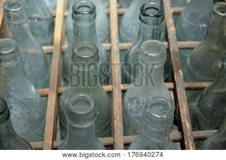 Wooden sectioned case of old glass bottles