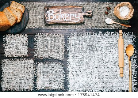 Rustic style template for food and drink industry. Burlap frames on dark wood background with flour pack and sliced bread. Wooden  cutting board with text 'Bakery' as title bar