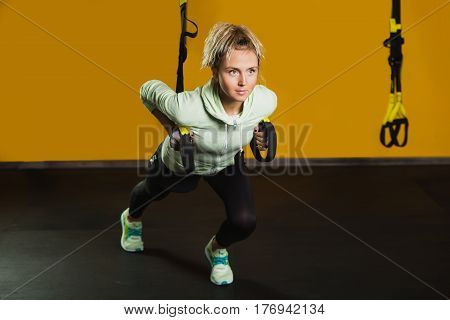 Sporty woman doing hand exercises with suspension straps at modern gym copy space for text. Suspension training for slim body