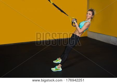 Sporty woman pull suspension straps training the muscles of the hands at sport Club. Suspension training for slim body