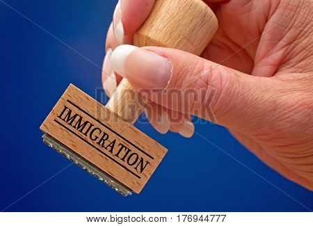 Immigration - female hand with stamp on blue background
